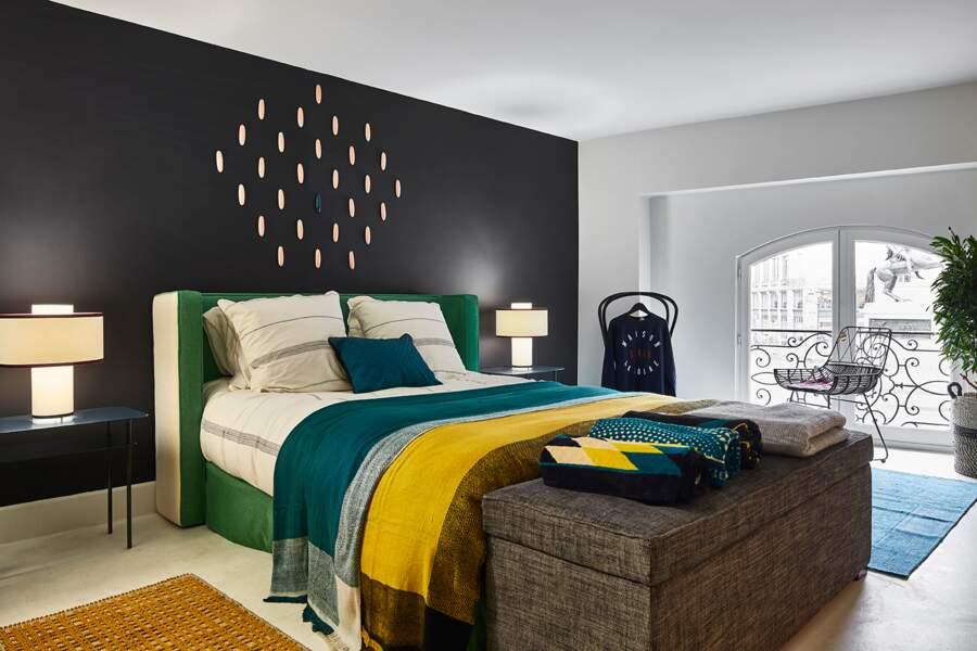 Chambre design avec mur noir et linge coloré