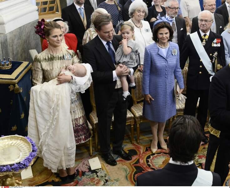 Nicolas est surveillé par Leonore, sa grande soeur, dans les bras de leur papa