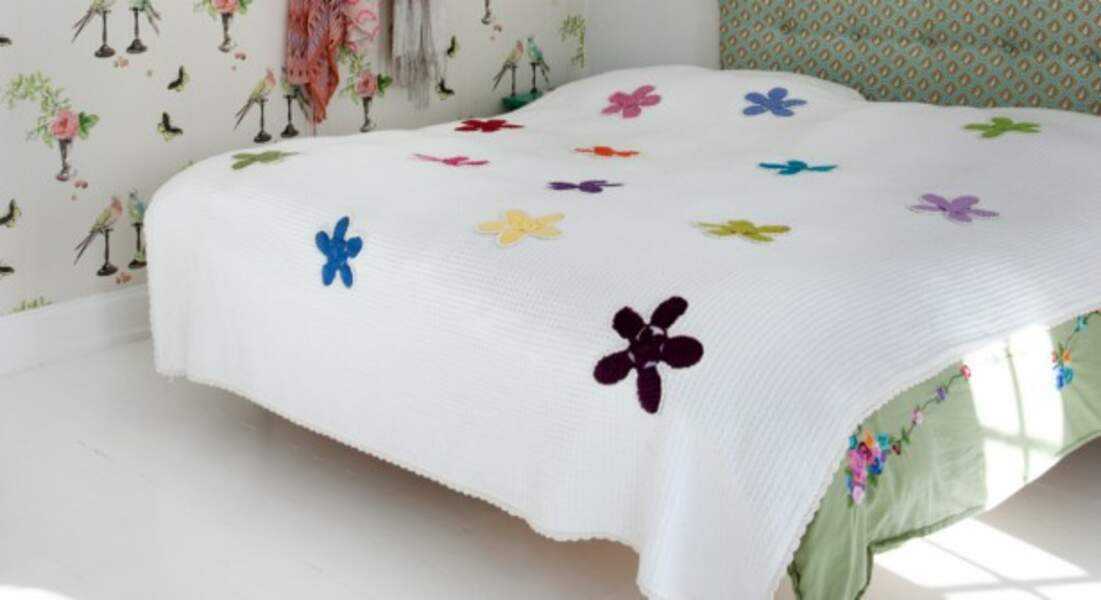 Une fleur crochetée à coudre sur un dessus de lit