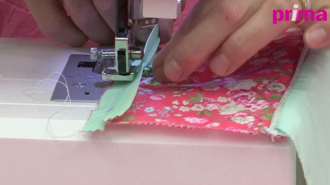 Cousez la fermeture à glissière à la machine sur le tissu floral au point droit