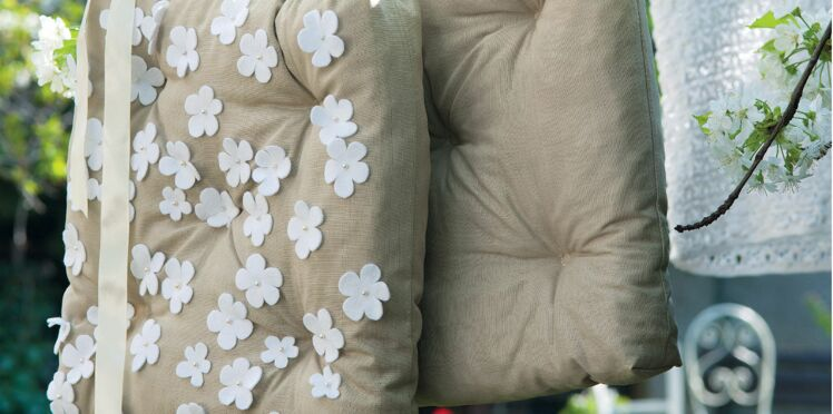 Un coussin printanier décoré de fleurs en feutrine