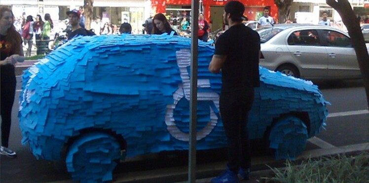 Une voiture garée sur une place pour handicapés transformée en panneau géant