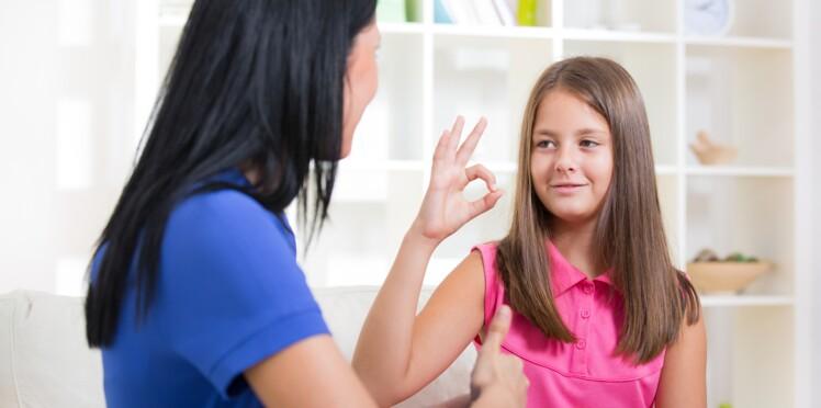 Une petite fille chante en langue des signes pour communiquer avec les enfants sourds