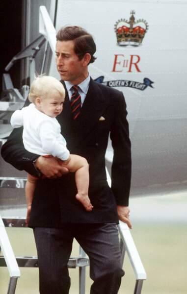 Le prince William dans les bras de son père Charles, prince de Galles, à l'aéroport d'Aberdeen en Écosse, en 1983.