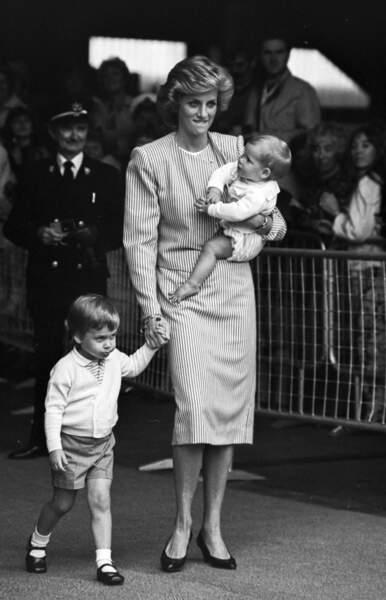 La princesse Diana portant Harry et tenant le prince William par la main, en 1985.