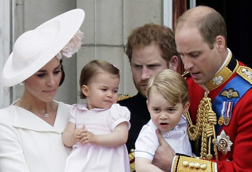La princesse Charlotte, dans les bras de sa mère, entouré par son frère George, son père William et son oncle Harry, le 11 juin 2016, sur le balcon de Buckingham Palace.