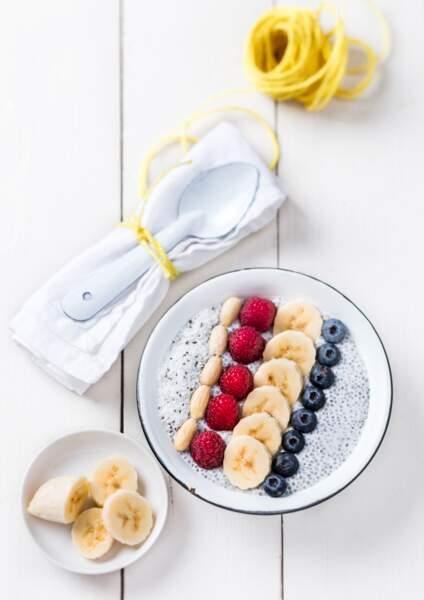 Porridge de graines de chia à la banane, aux amandes, aux framboises, à la poudre de noix de coco et aux myrtilles