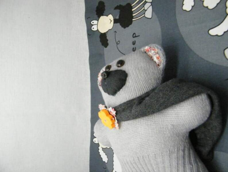 Un ourson en laine dans un vieux pull